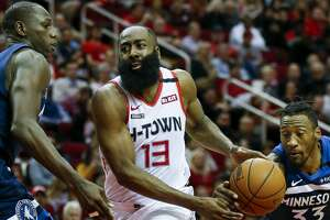 Minnesota Timberwolves forward Robert Covington (33) steals the ball away from Houston Rockets guard James Harden (13) during the first half of an NBA game at the Toyota Center Saturday, Jan. 11, 2020, in Houston.