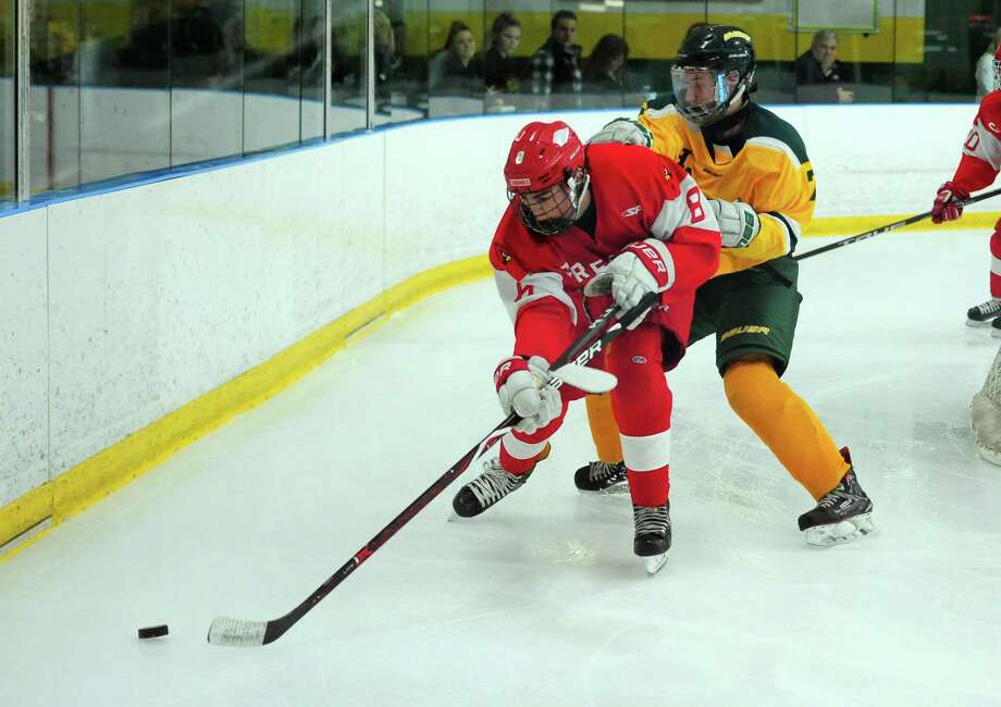 Greenwich's Benjamin Bates moves the puck as Hamden's Alan Cozzolino defends on Saturday. Photo: Christian Abraham / Hearst Connecticut Media / Connecticut Post