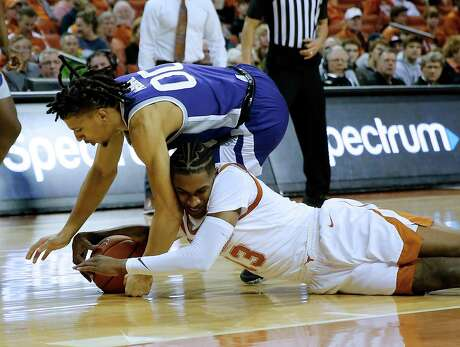 The Longhorns' Jase Febres battles for Kansas State's Mike McGuirl for a loose ball.