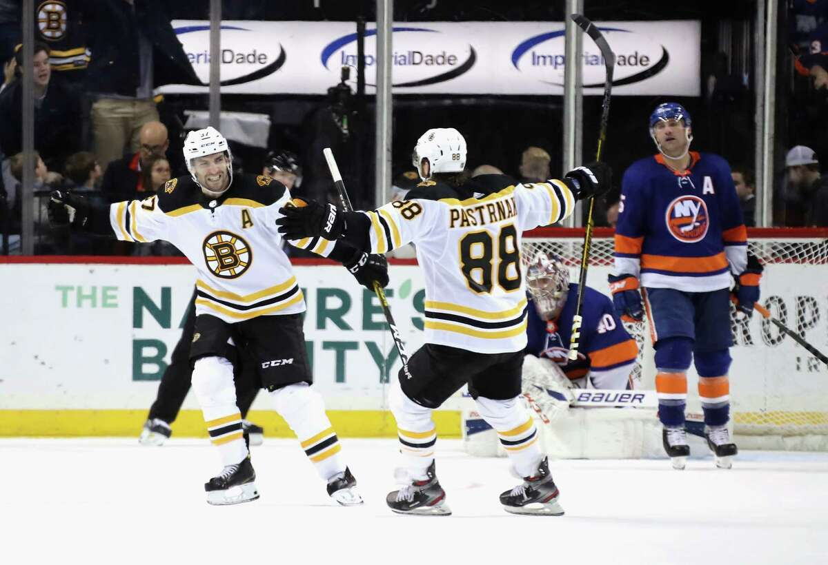 NEW YORK, NEW YORK - JANUARY 11: Patrice Bergeron #37 of the Boston Bruins (L) celebrates his game winning power-play goal at 2:33 of overtime against the New York Islanders and is joined by David Pastrnak #88 (R) at the Barclays Center on January 11, 2020 in the Brooklyn borough of New York City. (Photo by Bruce Bennett/Getty Images)