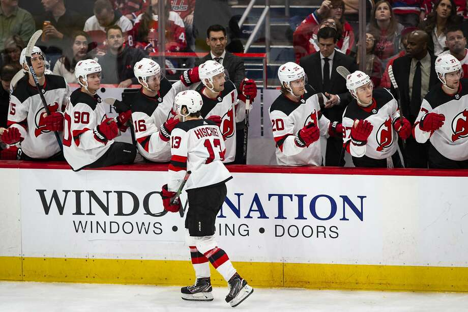 Devils center Nico Hischier (13) high-fives his teammates after scoring during the first period and he scored later to help New Jersey beat Washington. Photo: Al Drago / Associated Press