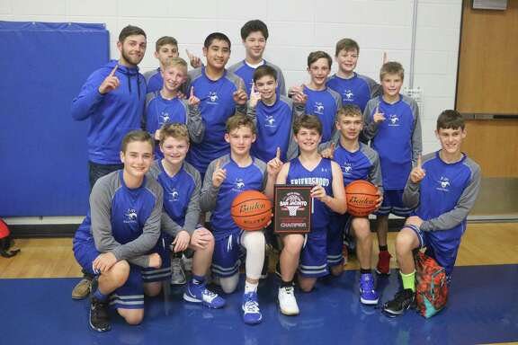 Coach Brandon Hollier and his happy band of seventh graders pose for a team picture after staging a three-game winning streak on Saturday to win the 15th annual San Jacinto Invitational.