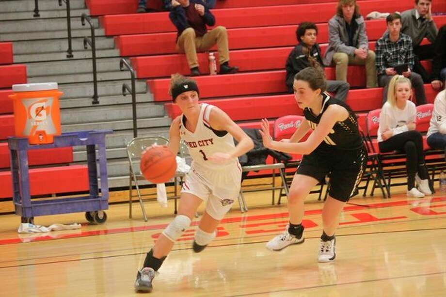 Reed City's Taylor Harrison (left) tries to make a move on the Reed City defense. (Pioneer photo/John Raffel)