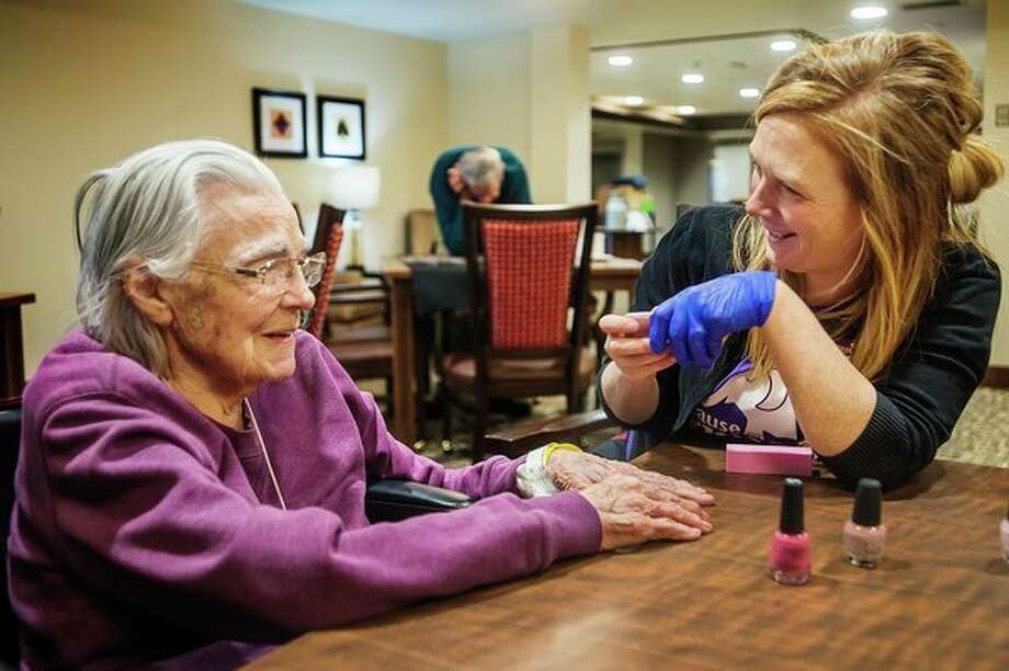 Dorothy Jonas, left, laughs with Melissa Hargis, life enrichment recreational therapist at Primrose Retirement Community, right, as Hargis paints her nails during a manicure session Thursday at Primrose. On the occasional slow news day, I will drive around town and look for things to photograph. When I stopped at Primrose and asked what the residents were up to, I was told about their weekly free manicure sessions. Chatting with Melissa Hargis and the two residents who had their nails painted, Dorothy Jonas and Barb Livingston, was the highlight of my week. (Katy Kildee/kkildee@mdn.net)