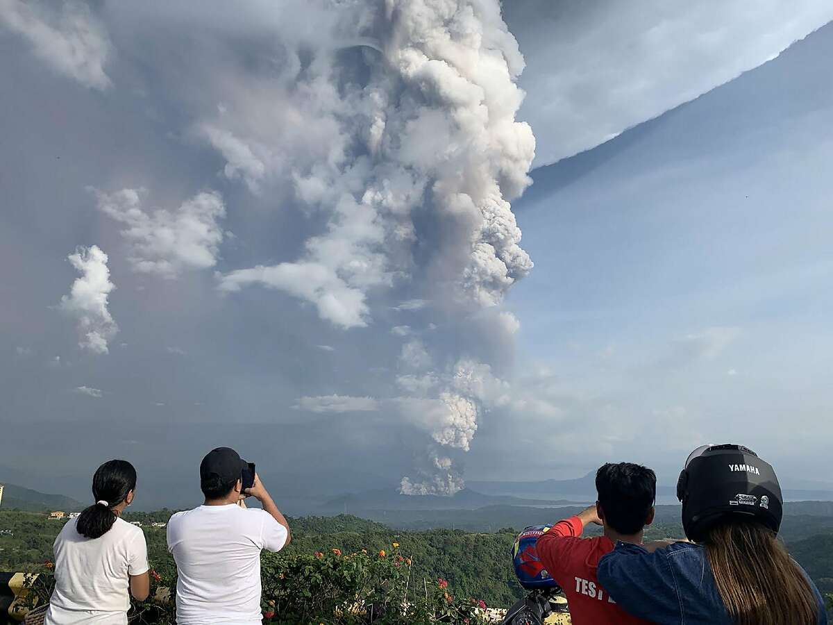 People take photos of a phreatic explosion from the Taal volcano as seen from the town of Tagaytay in Cavite province, southwest of Manila, on January 12, 2020. (Photo by Bullit MARQUEZ / AFP) (Photo by BULLIT MARQUEZ/AFP via Getty Images)