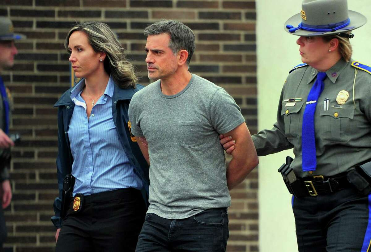Fotis Dulos is escorted to an awating police vehicle after being arrested and processed at State Police Troop G Headquarters in Bridgeport on Tuesday.
