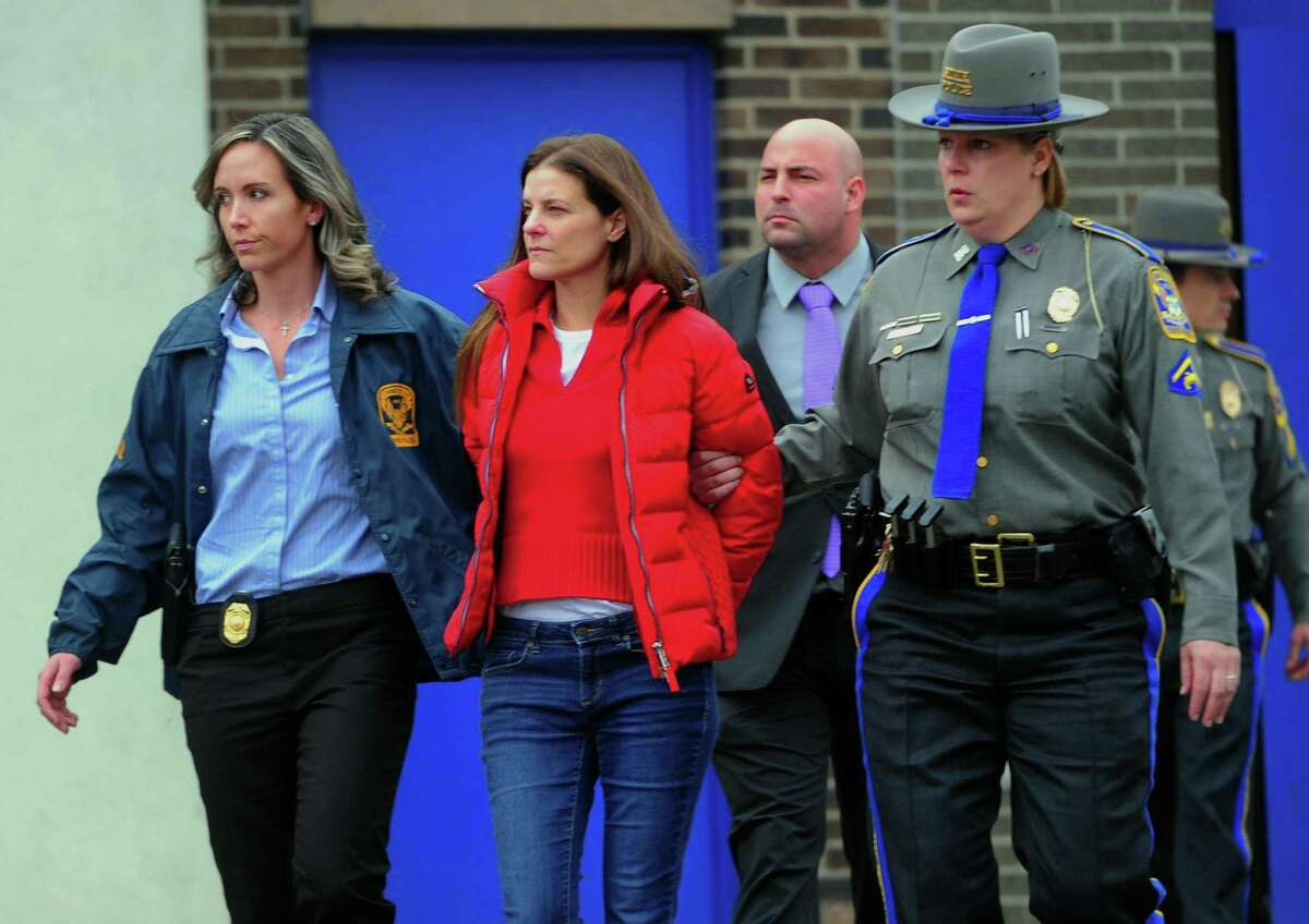 Michelle Troconis is escorted to an awating police vehicle after being arrested and processed at State Police Troop G Headquarters in Bridgeport on Tuesday.
