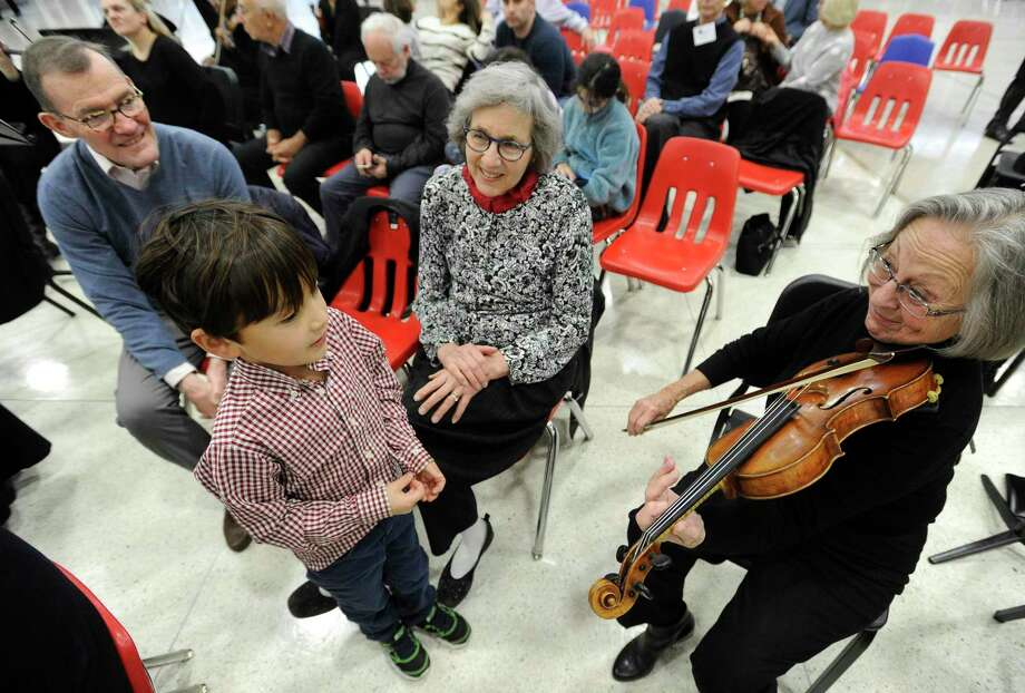 Violinists Pat Harada of Greenwich plays for Xander Schofield, 6, and grandparents James and Margot Mabie of Old Greenwich prior to the Greenwich Symphony Orchestra InsideOut Concert at Greenwich High School on Jan. 11, 2020 in Greenwich, Connecticut. . In collaboration with InsideOut Concerts, the GSO presented their very first immersive concert welcoming audience members to sit among the performers to experience a performance of Beethoven's Fifth Symphony. Photo: Matthew Brown / Hearst Connecticut Media / Stamford Advocate