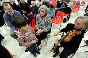 Violinists Pat Harada of Greenwich plays for Xander Schofield, 6, and grandparents James and Margot Mabie of Old Greenwich prior to the Greenwich Symphony Orchestra InsideOut Concert at Greenwich High School on Jan. 11, 2020 in Greenwich, Connecticut. . In collaboration with InsideOut Concerts, the GSO presented their very first immersive concert welcoming audience members to sit among the performers to experience a performance of Beethoven's Fifth Symphony.