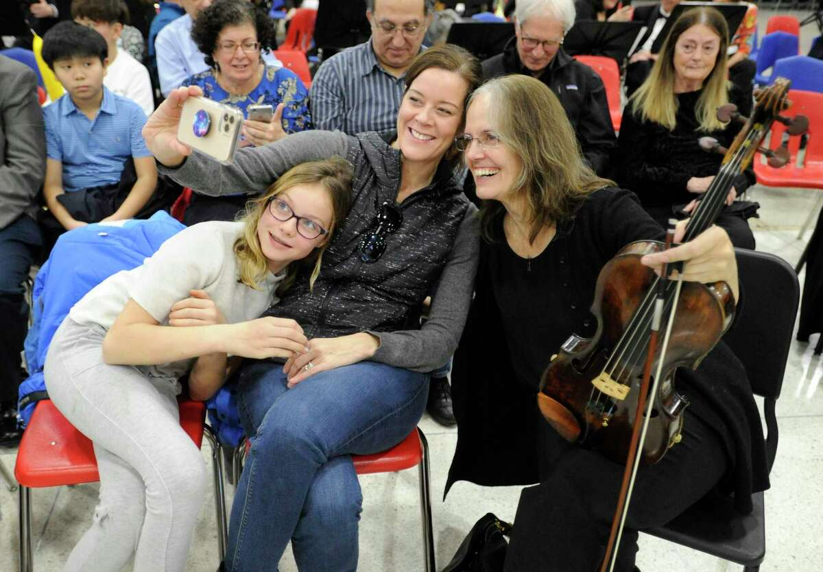 Allie Laverge, 10, of Riverside and her mother Kate take a selfie with a performer during the Greenwich Symphony Orchestra InsideOut Concert at Greenwich High School on Jan. 11, 2020 in Greenwich, Connecticut. . In collaboration with InsideOut Concerts, the GSO presented their very first immersive concert welcoming audience members to sit among the performers to experience a performance of Beethoven's Fifth Symphony.