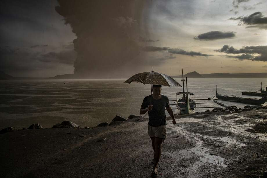 "A resident walks along a lakeside as Taal Volcano erupts on January 12, 2020 in Talisay, Batangas province, Philippines. Local authorities have begun evacuating residents near Taal Volcano as it began spewing ash up to a kilometer high Sunday afternoon. The Philippine Institute of of Volcanology and Seismology has raised the alert level to three out of five, warning of the volcano's continued ""magmatic unrest."" Photo: Ezra Acayan/Getty Images"