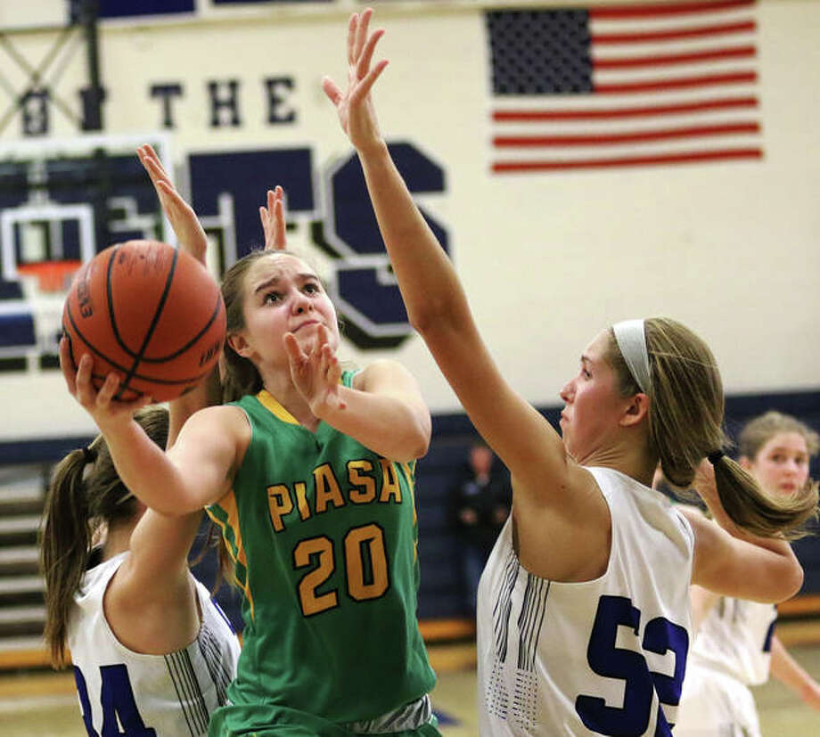 Southwestern's Korrie Hopkins (20) splits Greenville defenders and shoots around the Comets' Megan Hallemann in a SCC game Dec. 23 in Greenville. Hopkins scored 16 points Saturday in the Birds' victory over Vandalia in Piasa. Photo: Greg Shashack / The Telegraph