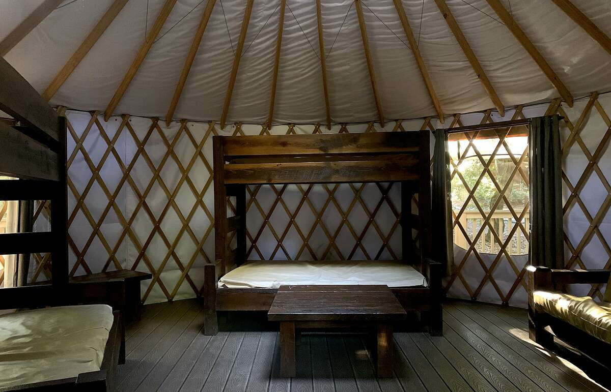 The interior of the camping yurts include table, sofa and beds for sleeping bags