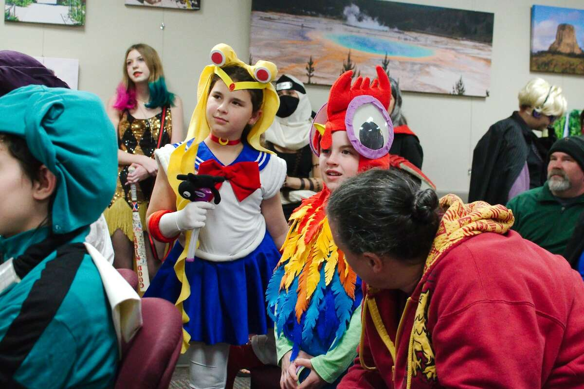 Ariana and Tristan Satterfield enjoy the show as cosplay fans compete in a costume contest during the Friendswood Library Zaki Con Sunday, Jan. 12.
