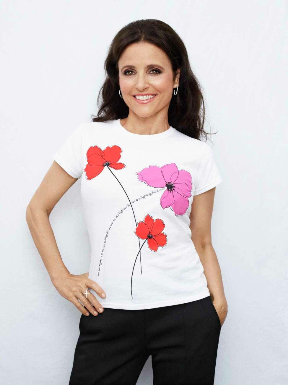 This undated image released by Saks Fifth Avenue shows actress Julia Louis-Dreyfus, revealed last September that she had been diagnosed with breast cancer, in a flower-adorned T-shirt as part of Saks Fifth Avenue's 20th year raising money through its Key to the Cure program. The limited edition shirt will sell for $35 at Saks stores Oct. 1-31, with 100 percent of proceeds going to the AiRS Foundation, a nonprofit Louis-Dreyfus supports for its work in helping women with the costs of breast reconstruction after mastectomy. (Saks Fifth Avenue via AP)