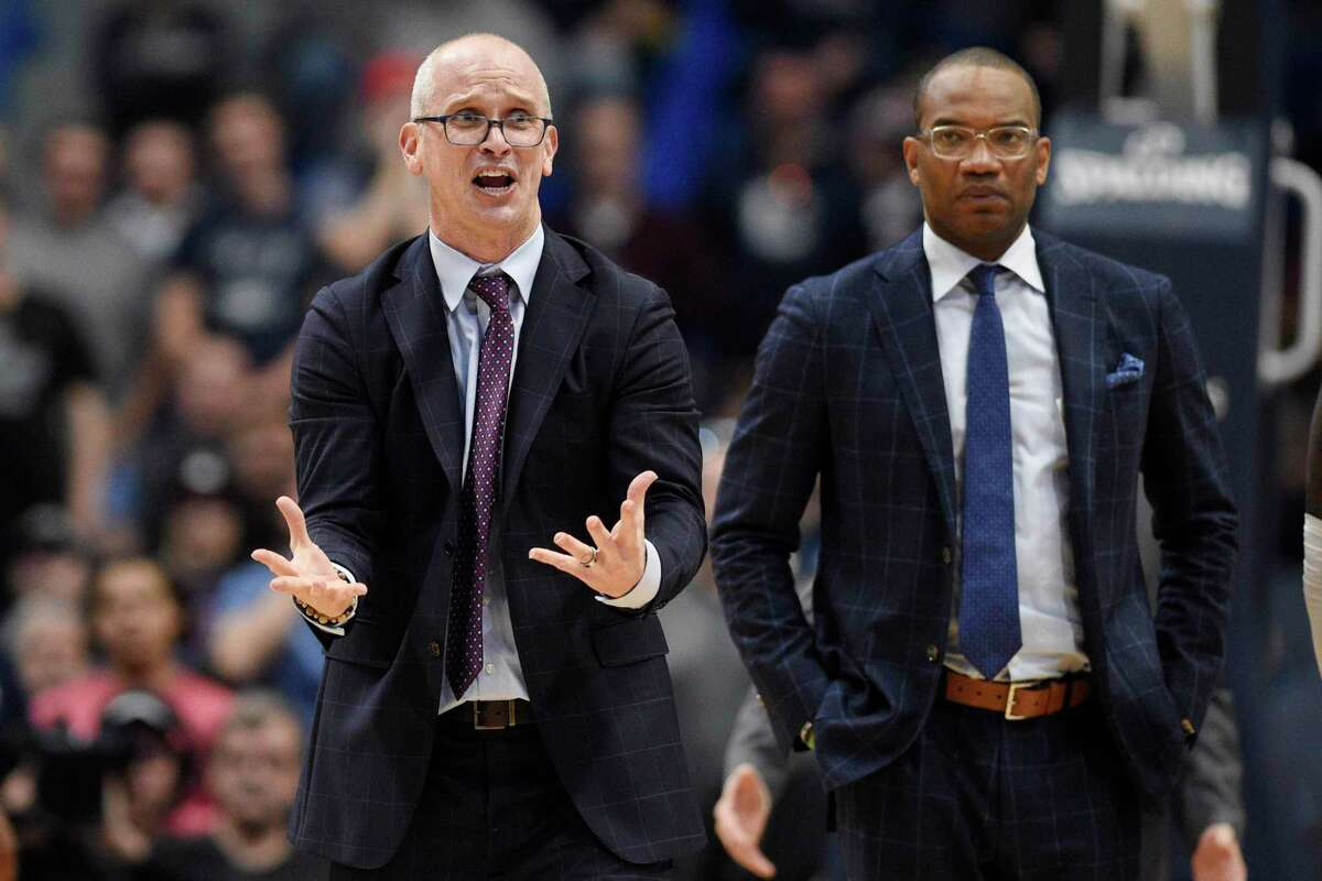 UConn coach Dan Hurley, left, reacts toward an official as assistant coach Kimani Young, right, looks on in the second half on Sunday.