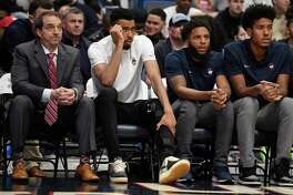 Connecticut's Tyler Polley, second from left, watches play from the bench in the first half of an NCAA basketball game, Sunday, Jan. 12, 2020, in Hartford, Conn. Polley is out for the season after he tore his left ACL at practice on Friday.