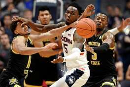 UConn's Sidney Wilson, center, fights for the ball between Wichita State's Noah Fernandes, left, and Trey Wade, right, in on Sunday in Hartford.Photo/Jessica Hill)