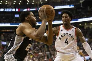 San Antonio Spurs' Rudy Gay, left, looks to make a play against Toronto Raptors' Rondae Hollis-Jefferson during first-half NBA basketball game action in Toronto, Sunday, Jan. 12, 2020. (Chris Young/The Canadian Press via AP)