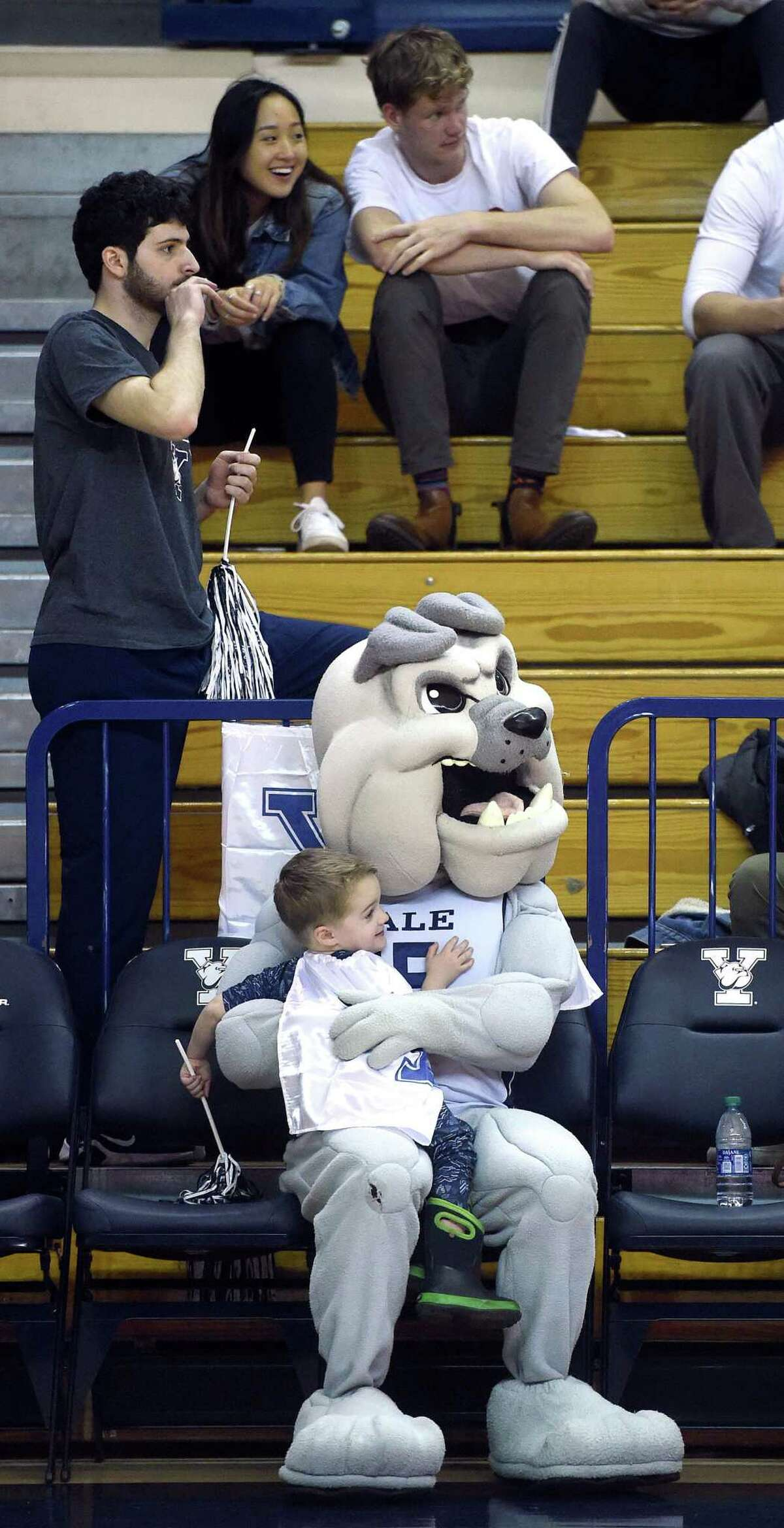 Clark Hetherington, 3, of Guilford sits in the lap of the Yale Bulldog mascot during Sunday's game against Johnson & Wales.