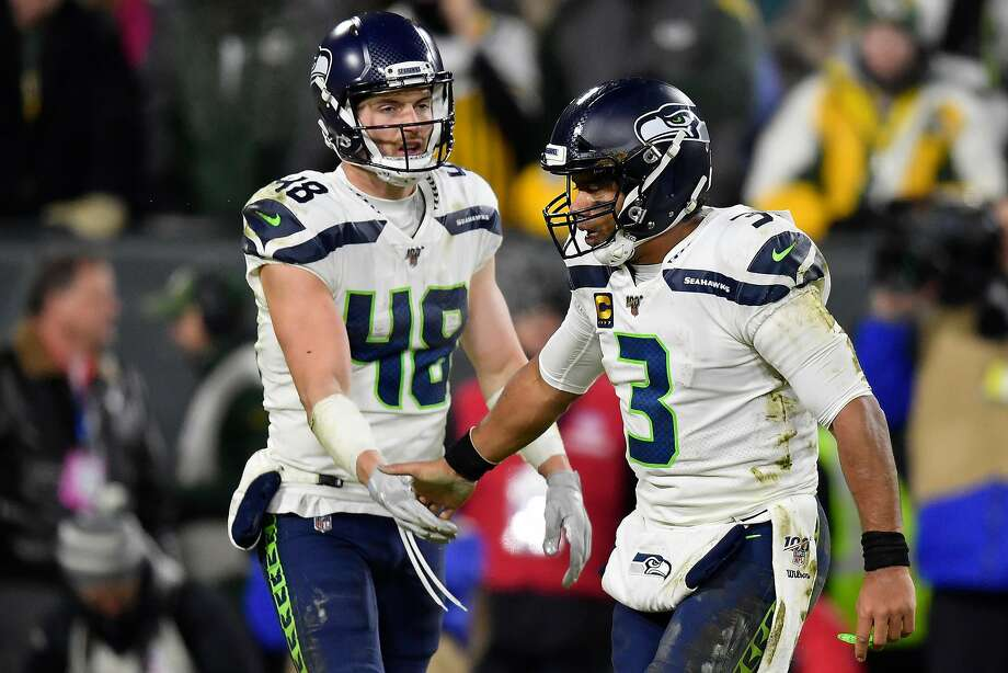 GREEN BAY, WISCONSIN - JANUARY 12: Jacob Hollister #48 of the Seattle Seahawks and teammate Russell Wilson #3 celebrate after a touchdown  against the Green Bay Packers in the third quarter of the NFC Divisional Playoff game at Lambeau Field on January 12, 2020 in Green Bay, Wisconsin. (Photo by Quinn Harris/Getty Images) Photo: Quinn Harris, Getty Images