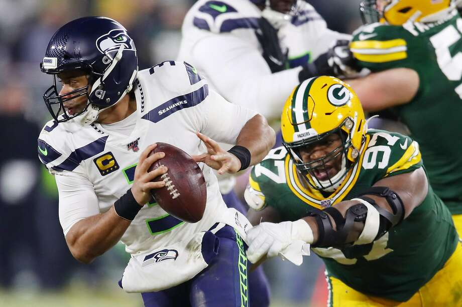 GREEN BAY, WISCONSIN - JANUARY 12: Kenny Clark #97 of the Green Bay Packers attempts to tackle Russell Wilson #3 of the Seattle Seahawks during the first half in the NFC Divisional Playoff game at Lambeau Field on January 12, 2020 in Green Bay, Wisconsin. (Photo by Gregory Shamus/Getty Images) Photo: Gregory Shamus, Getty Images
