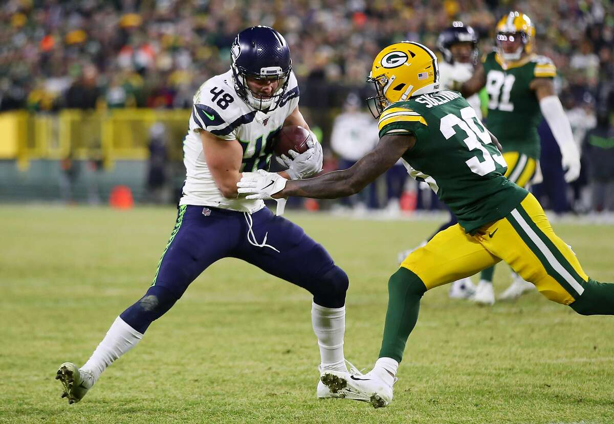 GREEN BAY, WISCONSIN - JANUARY 12: Chandon Sullivan #39 of the Green Bay Packers attempts to tackle Jacob Hollister #48 of the Seattle Seahawks in the NFC Divisional Playoff game at Lambeau Field on January 12, 2020 in Green Bay, Wisconsin. (Photo by Gregory Shamus/Getty Images)