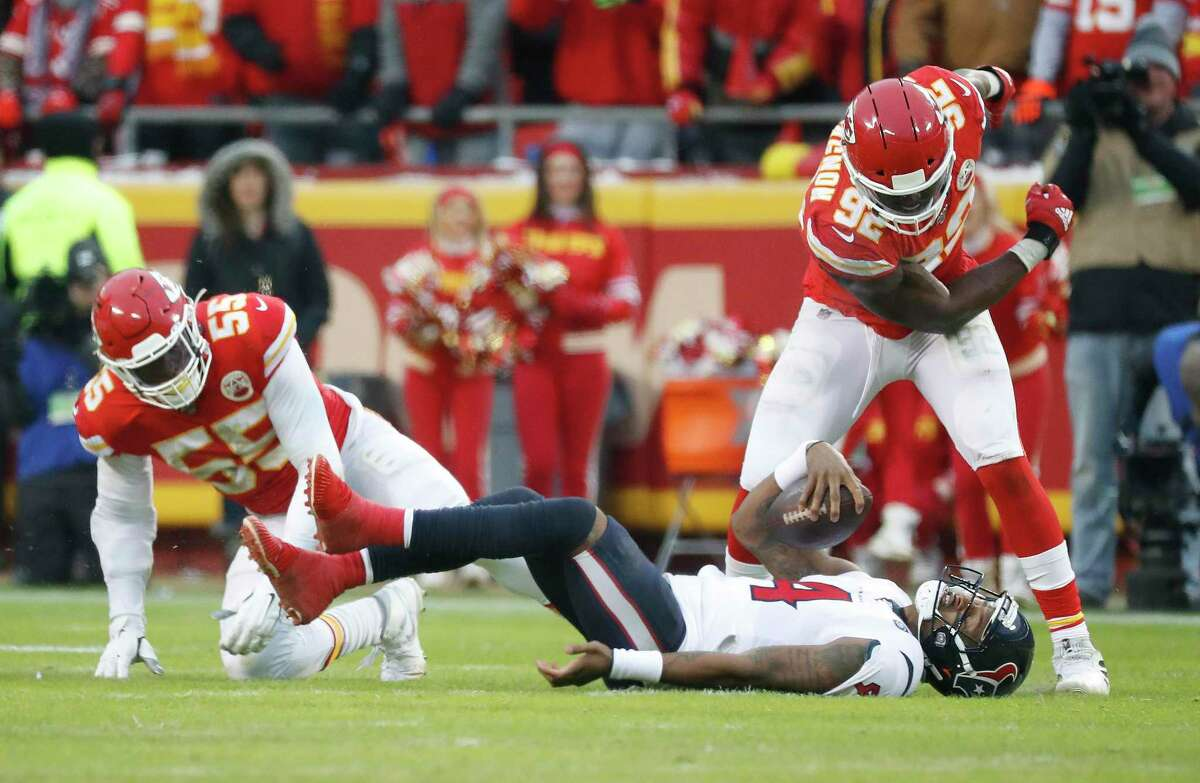 Houston Texans quarterback Deshaun Watson (4) lies on the turf after getting brought down by Kansas City Chiefs defensive ends Tanoh Kpassagnon (92) and Frank Clark (55) in the third quarter of an AFC divisional playoff game at Arrowhead Stadium on Sunday, Jan. 12, 2020, in Kansas City, Mo.