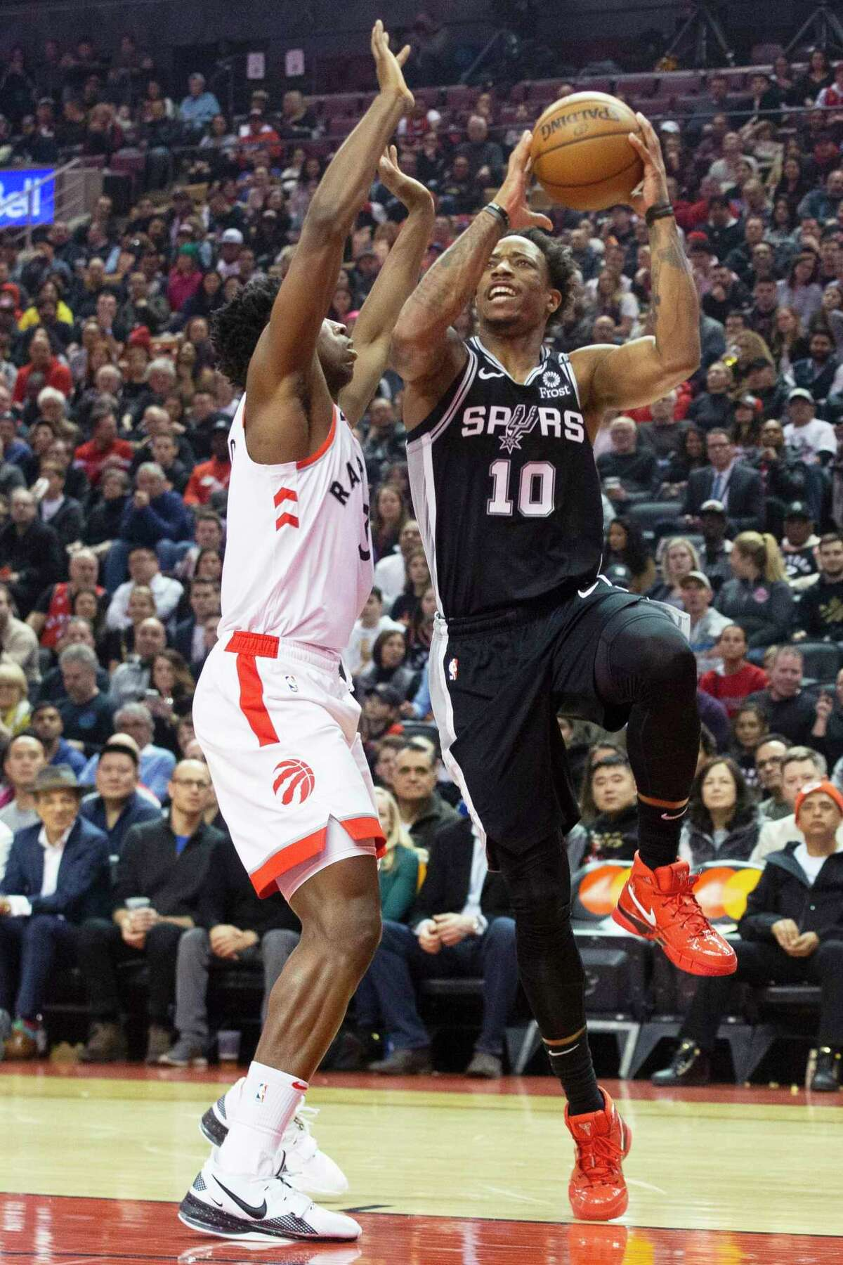 The Spurs' DeMar DeRozan, right, shoots on the Raptors' OG Anunoby in the first half on Sunday. DeRozan had his 11th straight game with at least 21 points.