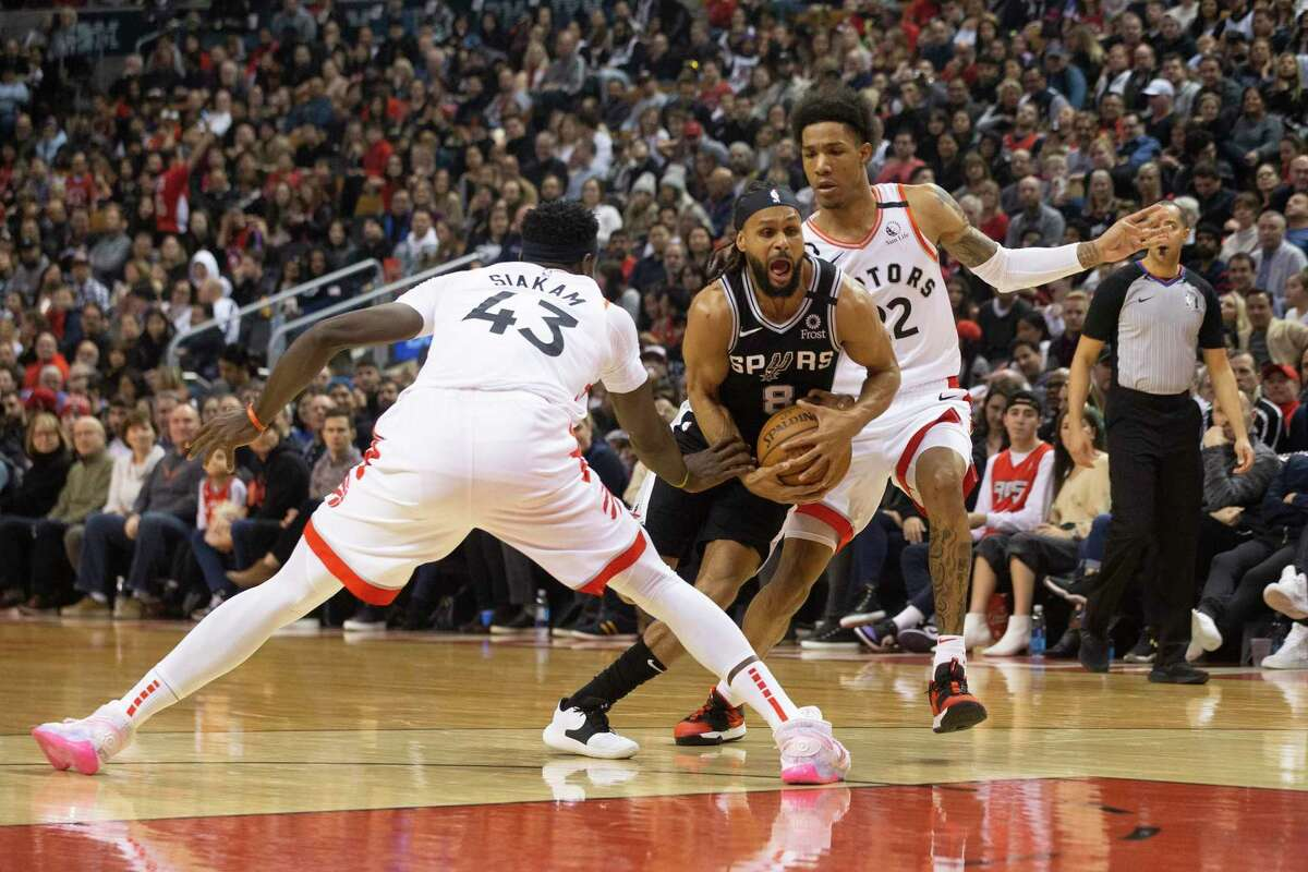 The Spurs' Patty Mills, center, drives between the Raptors' Pascal Siakam and Patrick McCaw in Toronto on Sunday.