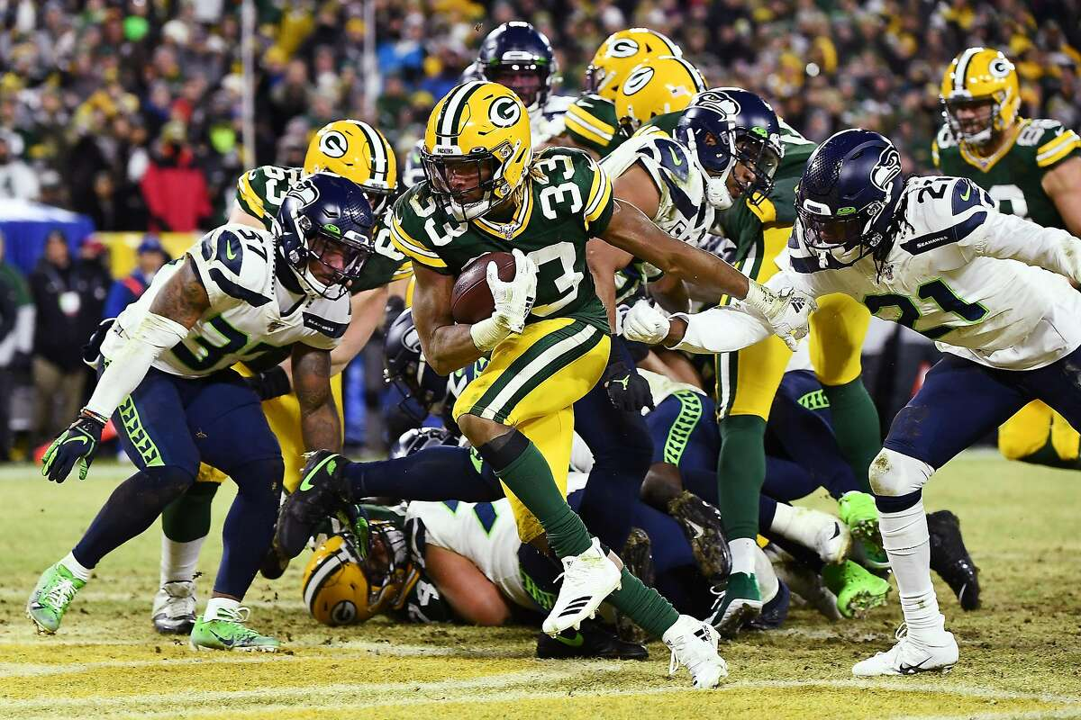 GREEN BAY, WISCONSIN - JANUARY 12: Aaron Jones #33 of the Green Bay Packers rushes for a touchdown during the second quarter against the Seattle Seahawks in the NFC Divisional Playoff game at Lambeau Field on January 12, 2020 in Green Bay, Wisconsin. (Photo by Stacy Revere/Getty Images)