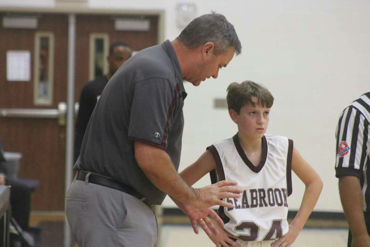 Seabrook Intermediate eighth-grade coach Darryl Menard holds a quick strategy meeting with Grayson Mullen during Saturday's consolation championship at Queens Intermediate. The Spartans were trying to protect a slim lead against Huffman Middle School.
