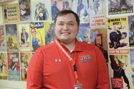 Mike Burke and some reproduction posters from World Wars I and II in his Jacksonville High School classroom.