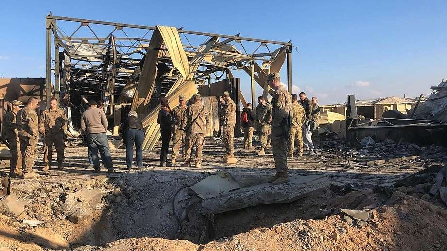 U.S. troops gather at the site of a missile blast at Ain al-Asad Air Base in Iraq's western Anbar province. Photo: Qassim Abdul-Zahra / Associated Press