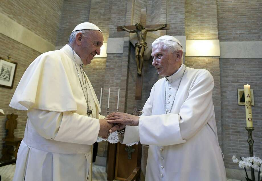 FILE - In this June 28, 2017, file photo, Pope Francis, left, and Pope Benedict XVI, meet each other on the occasion of the elevation of five new cardinals at the Vatican. Retired Pope Benedict XVI has broken his silence to reaffirm the value of priestly celibacy, co-authoring a bombshell book at the precise moment that Pope Francis is weighing whether to allow married men to be ordained to address the Catholic priest shortage. (L'Osservatore Romano/Pool photo via AP, File) Photo: L'Osservatore Romano, Associated Press
