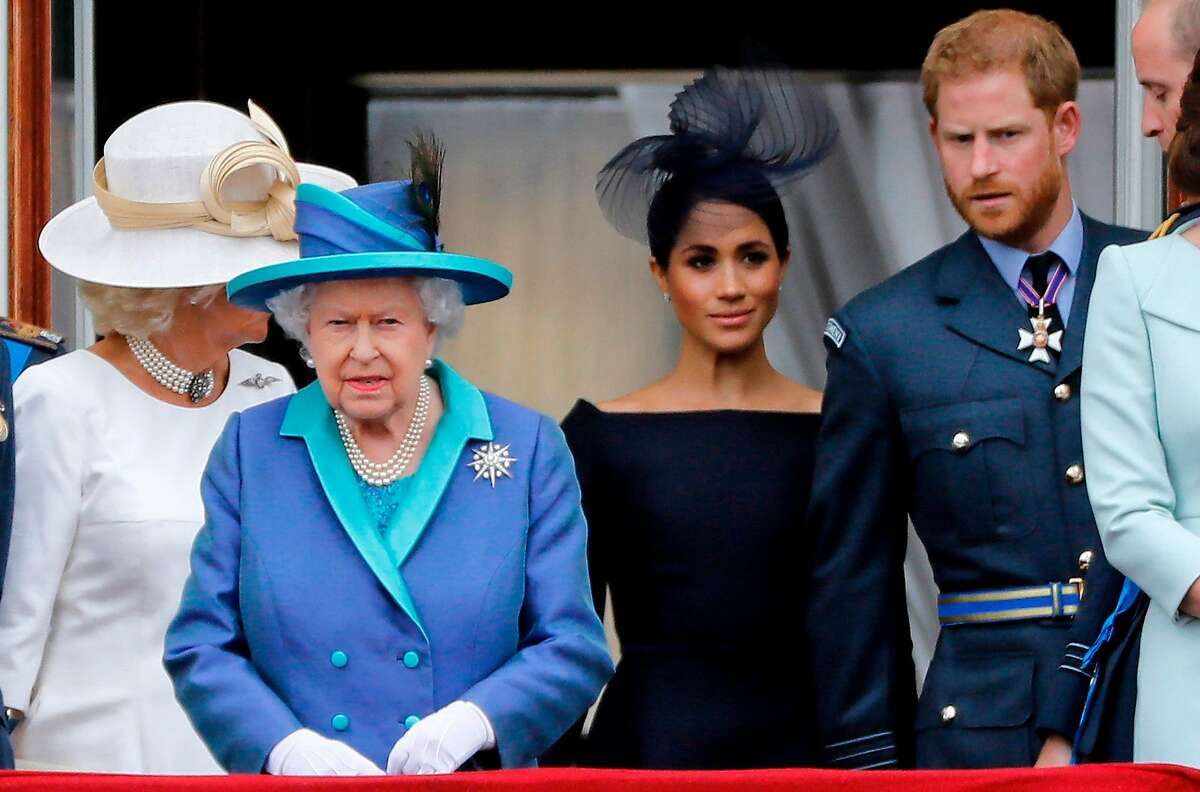 In this file photo taken on July 10, 2018 (L-R) Britain's Camilla, Duchess of Cornwall, Britain's Queen Elizabeth II, Meghan, Duchess of Sussex, Britain's Prince Harry, Duke of Sussex, and Britain's Prince William, Duke of Cambridge come onto the balcony of Buckingham Palace to watch a military fly-past to mark the centenary of the Royal Air Force (RAF). - Britain's Queen Elizabeth II on January 13, 2020, said Prince Harry and his wife Meghan would be allowed to split their time between Britain and Canada while their future is finalised. The couple said last week they wanted to step back from the royal frontline, catching the family off guard and forcing the monarch to convene crisis talks about the pair's future roles.