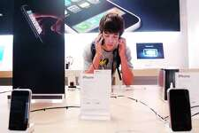 A customer makes a phone call with his new iPhone at the Apple Store in the Stamford Town Center. Apple has posted a message on the Stamford store's website that indicates the store is closing and will be replaced by Apple's new store at SoNo Collection mall in Norwalk, Conn.