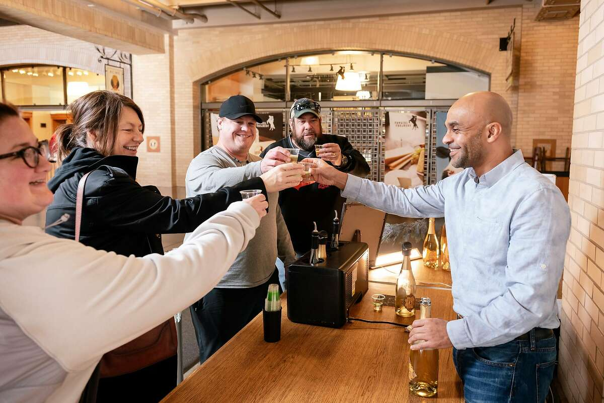 Owner Ayele Solomon, right, gives a cheers to guests Catherine Brown, left, Lori Liston, Bryan Brown, and Scott Liston during a tasting at Bee D'Vine Honey Wine Company's tasting bar in the Ferry Building in San Francisco, California, Thursday, January 9th, 2020.