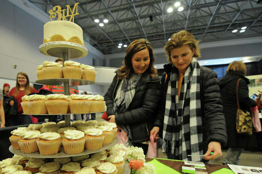 Mother of the groom Angie Daniels and mother of the bride Tracy Streeper, both of Bethalto, admire a cupcake-tiered wedding cake by The Cup during Sunday's Bridal Show at Lewis and Clark Community College Commons in Godfrey. Hundreds turned out for the event hosted by The Telegraph, The Intelligencer and On The Edge of the Weekend. Photo: Photos By David Blanchette|For The Intelligencer