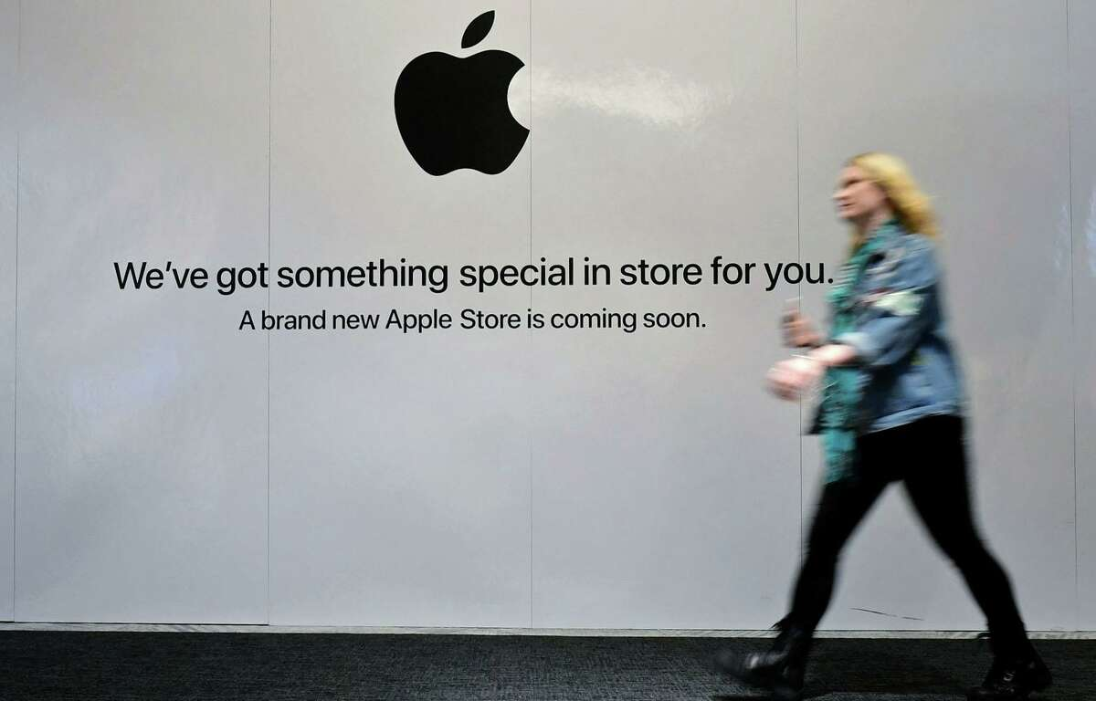 Shoppers walk past the sign heraldng the arrival of the Apple store in the new SoNo Collection mall Saturday, December 14, 2019, in Norwalk, Conn.