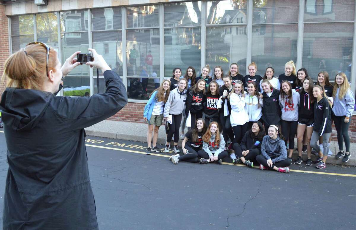 Karen Charlton of New Canaan grabs a photo of the New Canaan High School girls cross country team, which took part in the Walk-A-Thon for Save God's Kids, held at St. Aloysius Church, Saturday, Oct. 21, 2017, in New Canaan, Conn. The picture was taken in front of St. Aloysius School, which is near the previously mentioned St. Aloysius Church.