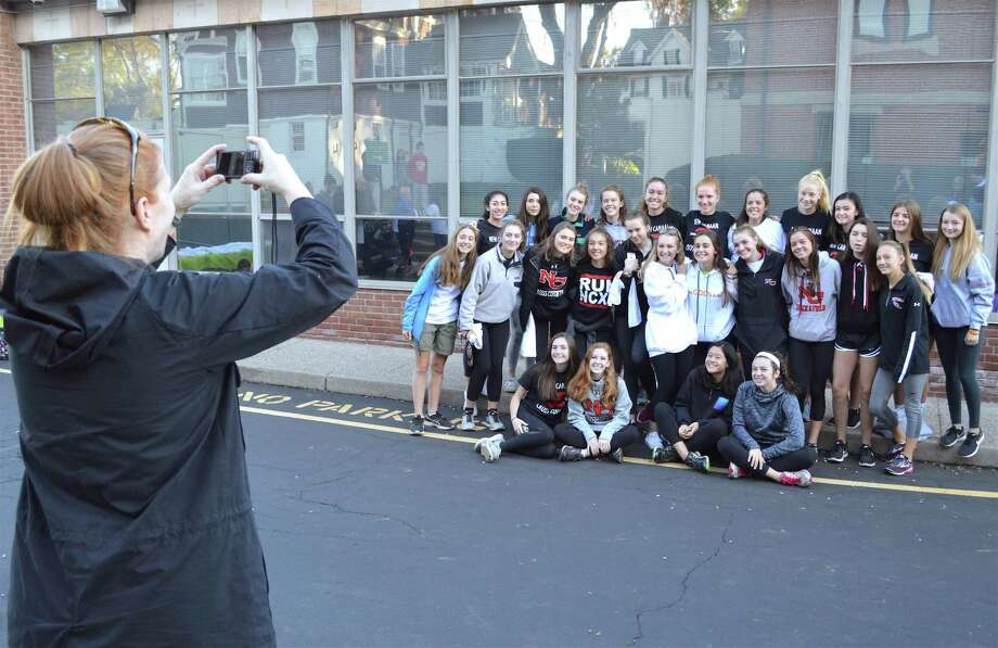 Karen Charlton of New Canaan grabs a photo of the New Canaan High School girls cross country team, which took part in the Walk-A-Thon for Save God's Kids, held at St. Aloysius Church, Saturday, Oct. 21, 2017, in New Canaan, Conn. The picture was taken in front of St. Aloysius School, which is near the previously mentioned St. Aloysius Church. Photo: Jarret Liotta / For Hearst Connecticut Media / New Canaan News Freelance