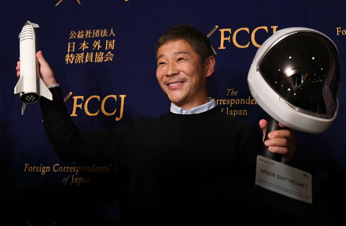 Yusaku Maezawa, entrepreneur and CEO of ZOZOTOWN and SpaceX BFR's first private passenger, poses with a miniature rocket and space helmet prior to start of a press conference at the Foreign Correspondents' Club of Japan in Tokyo on October 9, 2018.