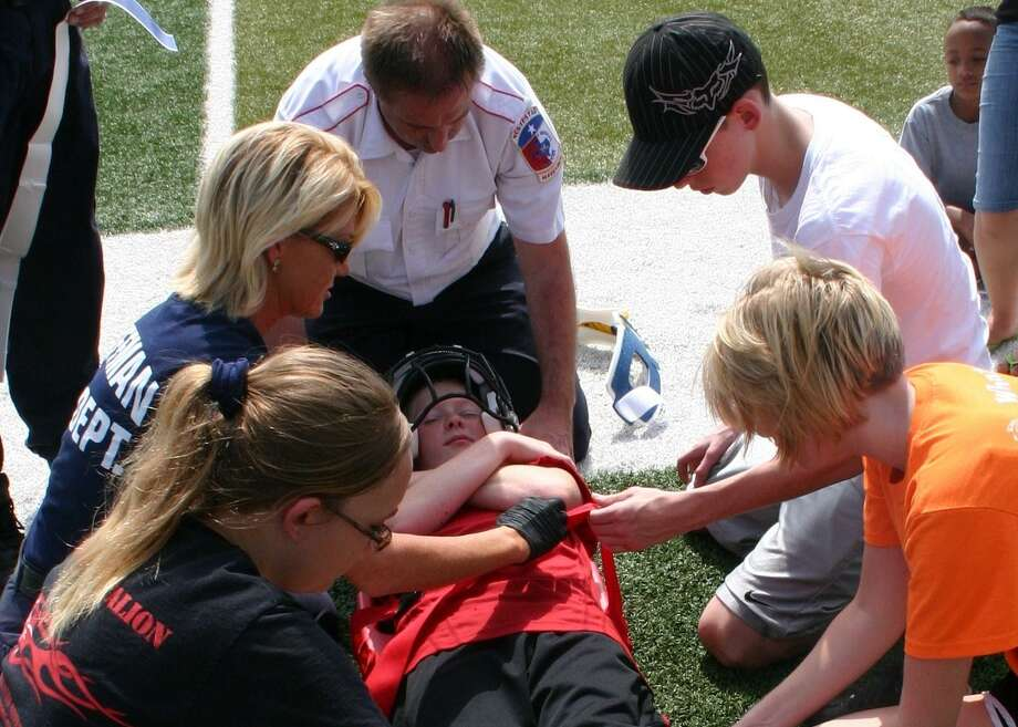 Huffman Independent School District student athletic trainers learn and practice how to handle certain emergencies. Taylor Daniels is an injured football player in this scenario. The teachers, counter clockwise, from the top, are Northstar EMS Operations Supervisor Heath Manson and Huffman Volunteer Fire Department Firefighter Norma McClure. Northstar and fire department personnel, along with Athletic Trainer Riley Wheeler, conducted for 13 students the training exercises, which were held July 27 at the Hargrave High School football stadium. Photo: STEPHEN THOMAS / Internal