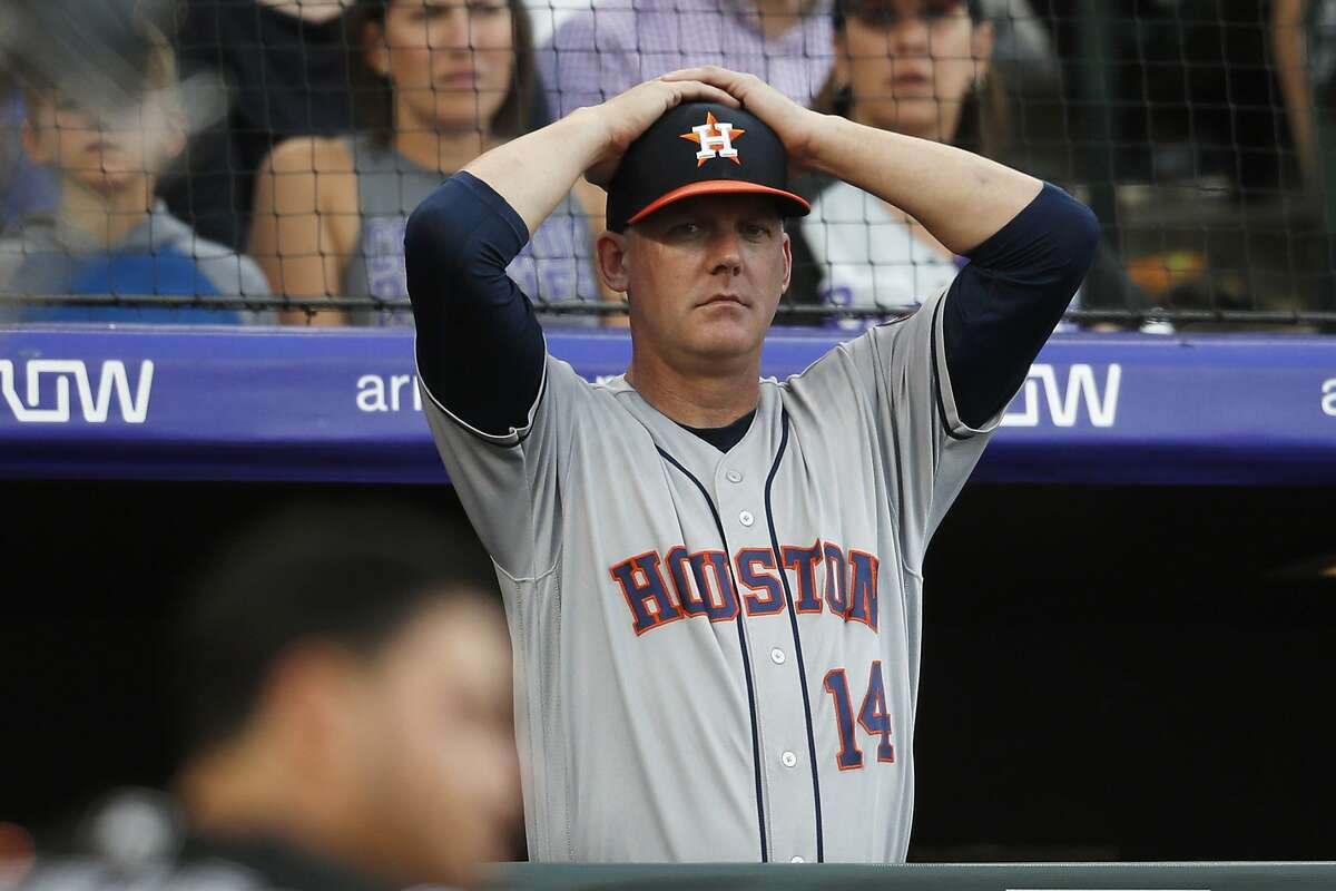 FILE - In this July 2, 2019, file photo, Houston Astros manager AJ Hinch reacts during a baseball game against the Colorado Rockies, in Denver. Houston manager AJ Hinch and general manager Jeff Luhnow were suspended for the entire season Monday, Jan. 13, 2020, and the team was fined $5 million for sign-stealing by the team in 2017 and 2018 season. Commissioner Rob Manfred announced the discipline and strongly hinted that current Boston manager Alex Cora - the Astros bench coach in 2017 - will face punishment later. Manfred said Cora developed the sign-stealing system used by the Astros. (AP Photo/David Zalubowski, File)
