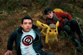 "This image released by Warner Bros. Pictures shows Justice Smith, left, the character Detective Pikachu, voiced by Ryan Reynolds, and Kathryn Newton in a scene from ""Pokemon Detective Pikachu."" (Warner Bros. Pictures via AP)"