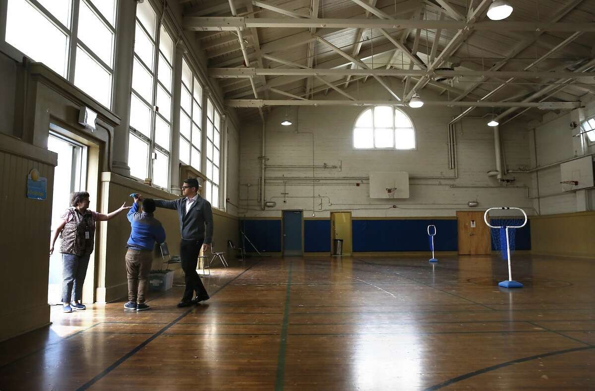 Principal Richard Zapien, (right) directs a student at the gymnasium, where the shelter would be located at Buena Vista Horace Mann K-8 school in San Francisco, Calif. This San Francisco public school is considering opening a family homeless shelter in one of the gyms to house students and their families who are homeless or need emergency shelter.