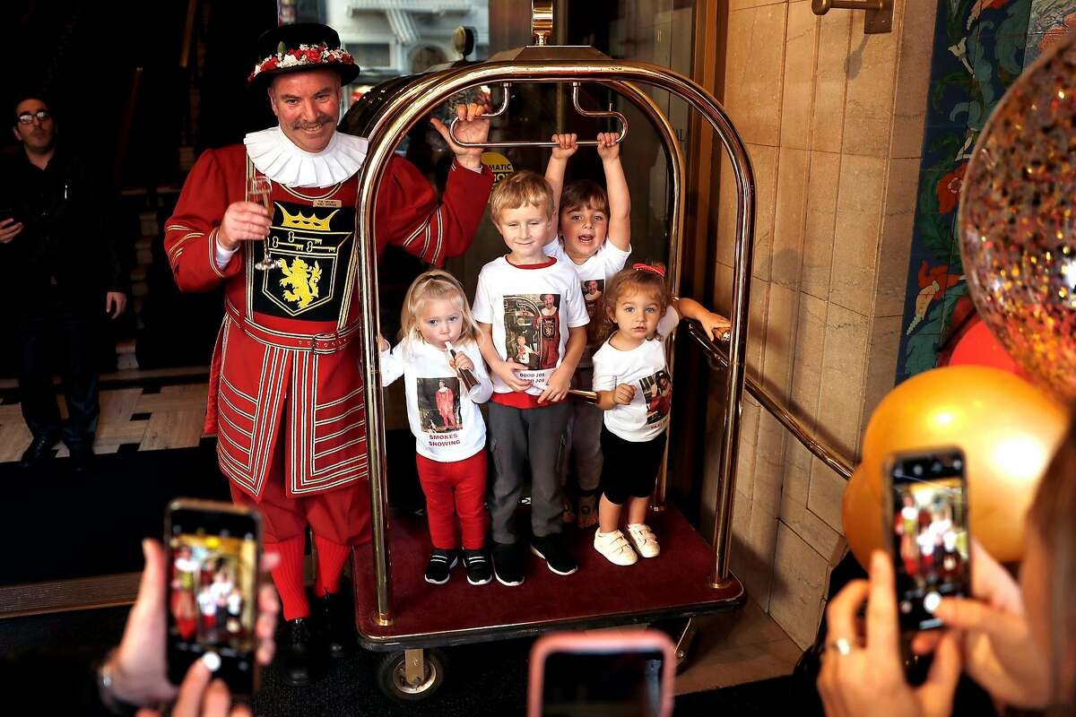 Beefeater doorman Tom Sweeney poses with his grandchildren at the end of his shift on the final day of his 43 year long career at the Sir Francis Drake Hotel in San Francisco, Calif., on Sunday, January 12, 2020.