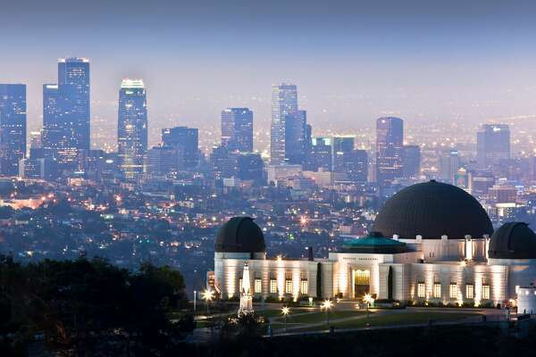 View of Griffith Observatory with downtown Los Angeles skyline in background.