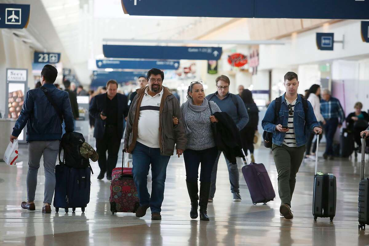 Javier Valencia (center left) and Maria Ojeda (center right), both of Guadalajara, walk arm and arm through Terminal B at Norman Y. Mineta San Jose International Airport on Tuesday, January 7, 2020 in San Jose, Calif.